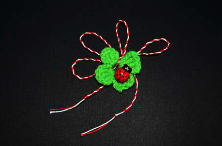 Handmade crocheted four-leaf clover with ladybug and red and white string, known as Martisor. It is a Romanian traditional symbol of the beginning of spring. Isolated on black background.