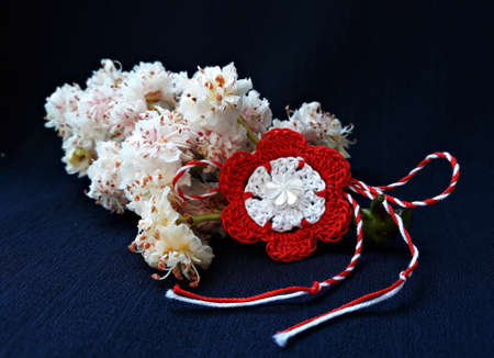 Handmade crocheted flower with red and white string, known as Martisor. It is a Romanian traditional symbol of the beginning of spring. Isolated on black background.