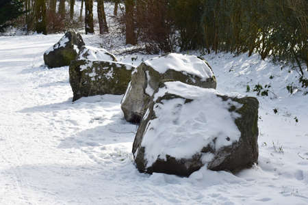 Decorative stones covered with snow in the park.