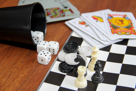 mix of goblet table games dice spanish poker cards chess and checkers