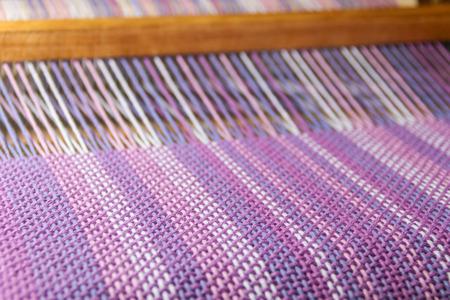 detail van stof in kamweefgetouw met ultraviolette en lila kleuren