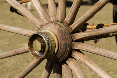 old wooden wheel and sulky bronze in the field Stock Photo