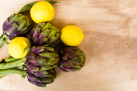 artichokes cooked with lemon and salt on rustic wooden background Archivio Fotografico