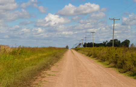 concept of distance with field road in the plain Stockfoto