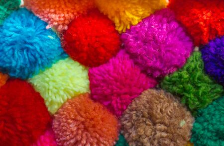 textured background of assorted and multicolored wool pom poms