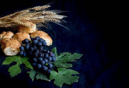 wheat grapes bread and crown of thorns on black background as a symbol of Christianity