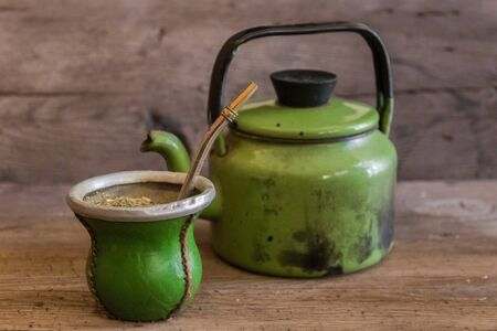 mate and kettle, traditional Argentine yerba mate infusion, on rustic wooden background