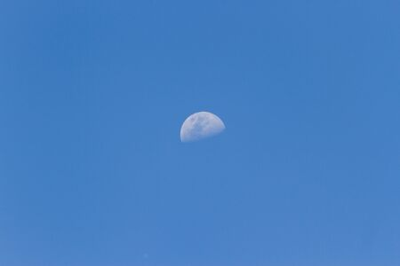 A horizontal shot of a half-moon visible during daylight in the blue sky