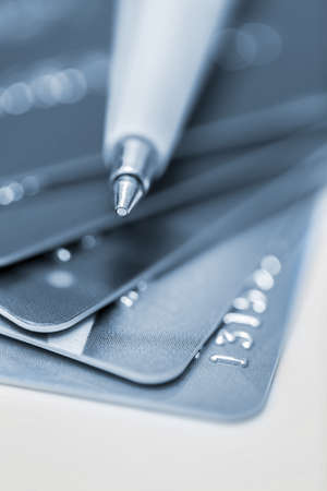 Macro photograph of credit cards with ballpoint pen on whirte background photo