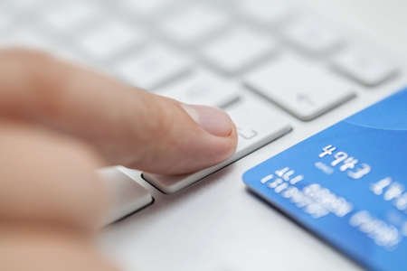 Man is entering credit card information to web site to complete shopping photo