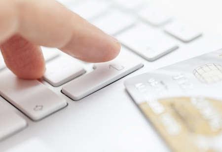 entering information: Man is entering credit card information to computer