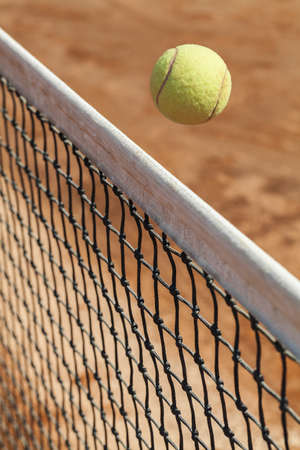 passing over: Close up photograph of a tennis ball passing over the net Stock Photo