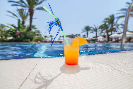icecube: Close-up photograph of a cocktail near the pool with a shallow depth of field