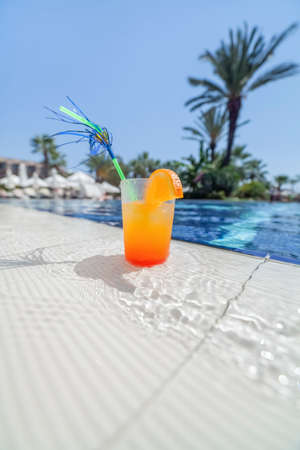 Close-up photograph of a cocktail near the pool with a shallow depth of field  photo