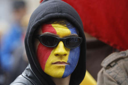 BUCHAREST, ROMANIA - OCTOBER 19, 2016:  A young man with his face painted in the Romanian and Moldovan flag colors attends a rally demanding the union between Romania and the Republic of Moldova.