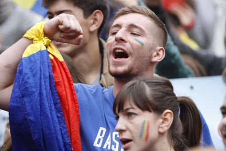 BUCHAREST, ROMANIA - OCTOBER 19, 2016:  A young woman and man with the Romanian and Moldovan flag painted on their cheeks attend a rally demanding the union between Romania and the Republic of Moldova. Editorial