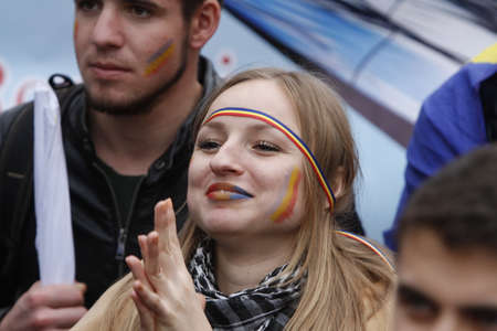 BUCHAREST, ROMANIA - OCTOBER 19, 2016:  A young woman with the Romanian and Moldovan flag painted on her cheeks attends a rally demanding the union between Romania and the Republic of Moldova.