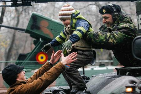batallón: Bucarest, Rumania - DICIEMBRE 1, 2010: Un niño está jugando en un tanque durante un desfile militar en el Día Nacional de Rumanía. Más de 3.000 soldados y personal de los organismos de seguridad participan en los desfiles masivos en el Día Nacional de Rumanía.