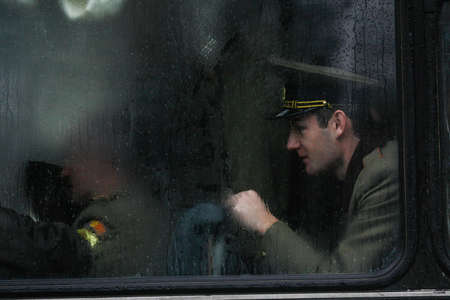 paramilitary: BUCHAREST, ROMANIA - DECEMBER 1, 2010: A military is seen behind a bus window during a military parade. More than 3,000 soldiers and personnel from security agencies take part in the massive parades on National Day of Romania.