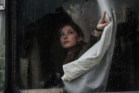 paramilitary: BUCHAREST, ROMANIA - DECEMBER 1, 2010: A military woman is seen behind a bus window during a military parade. More than 3,000 soldiers and personnel from security agencies take part in the massive parades on National Day of Romania.