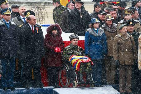 batallón: BUCAREST, ROMANIA - 1 de diciembre de 2014: Un veterano de guerra participa, junto al presidente rumano y otros funcionarios, en un desfile militar en el Día Nacional de Rumania. Más de 3,000 soldados y personal de agencias de seguridad participan en el massiv