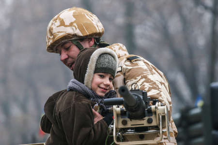 BUCHAREST, ROMANIA - DECEMBER 1, 2008: A soldier is paying with a child during a military parade on National Day of Romania. More than 3,000 soldiers and personnel from security agencies take part in the massive parades on National Day of Romania.
