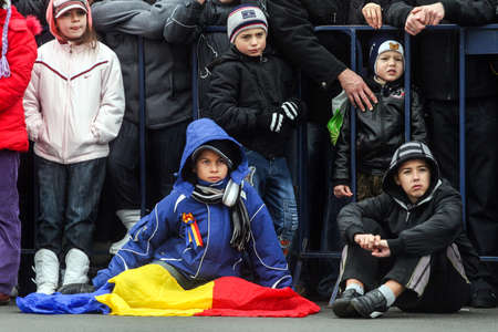 paramilitary: BUCHAREST, ROMANIA - DECEMBER 1, 2009: Children are watching the military parade on National Day of Romania. More than 3,000 soldiers and personnel from security agencies take part in the massive parades on National Day of Romania. Editorial