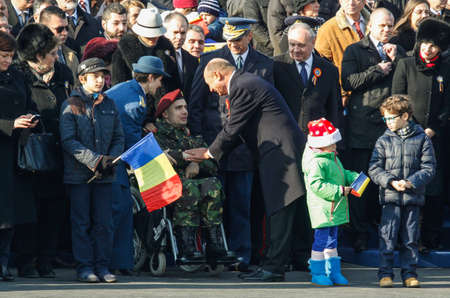 BUCHAREST, ROMANIA - DECEMBER 1, 2013: Romanian president Traian Basescu salutes a war veteran during a military parade on National Day of Romania. More than 3,000 soldiers and personnel from security agencies take part in the massive parades on National
