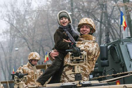 batallón: BUCAREST, ROMANIA - 1 de diciembre de 2008: Un soldado está pagando con un niño durante un desfile militar en el Día Nacional de Rumania. Más de 3,000 soldados y personal de las agencias de seguridad participan en los desfiles masivos en el Día Nacional de Rumania. Editorial