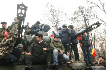 paramilitary: BUCHAREST, ROMANIA - DECEMBER 1, 2009: Children are playing on a tank during a military parade on National Day of Romania. More than 3,000 soldiers and personnel from security agencies take part in the massive parades on National Day of Romania.