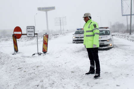 BUCHAREST, ROMANIA - January 06, 2017: A police car blocks the access on A2 motorway to the main harbor of Black Sea, Constanta, due to the snow storm.