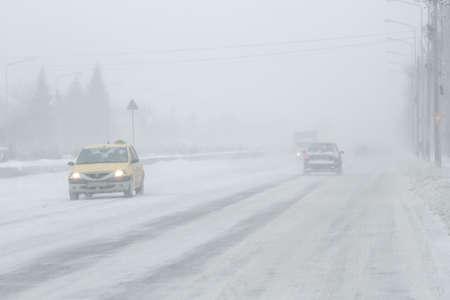 Bukarest, Rumänien, 25. Januar 2016: Die Autos sind vorbei auf einer verschneiten Straße in einem Schneesturm in Bukarest.