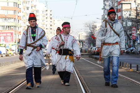 whips: Bucharest, Romania, December 30, 2012: Carolers dressed in national costumes and wearing whips are performing in a tram station in Bucharest.