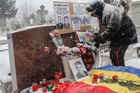 dictator: Bucharest, Romania, January 26, 2014: A man puts a map of Romania at the grave of Romanias late communist dictator Nicolae Ceausescu, during commemoration of his birthday. Year after year Romanias nostalgic Communists gather to mourn Ceausescu, who was