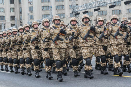 paramilitary: BUCHAREST, ROMANIA - November 29, 2015: Military are marching during a rehearsal for National Day of Romania military parade in Bucharest. More than 3,000 soldiers and personnel from security agencies take part in the massive parades on National Day of Ro