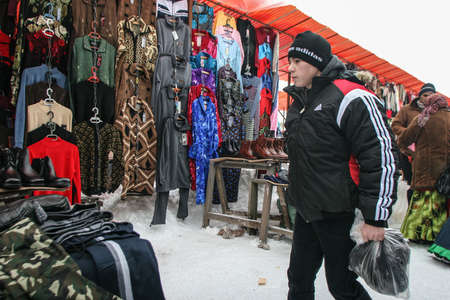 Calugareni, Romania, December 20, 2009: A young man is looking at different products in the animal market in Calugareni. Before Christmas, animal breeders are selling and sacrificing their animals in animal markets and vendors are selling different produc
