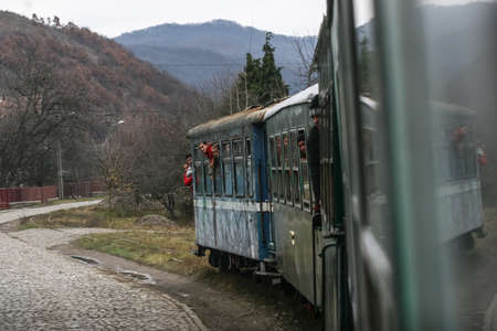 holydays: Brad, Romania, December12, 2009: Tourists are travel in an old steamed cog train in Brad, on winter holydays.