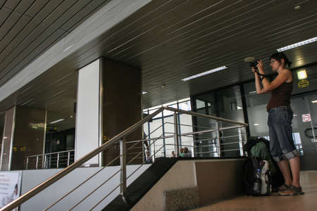 coanda: Bucharest, Romania, August 14, 2009: A woman is taking photos in the Henry Coanda airport.