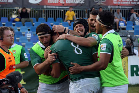 rival: BUCHAREST, ROMANIA - June 24, 2017: Andre Arruda from Brasil is celebrated by his team mates after grounding the ball in rugby test game between Romania and Brasil, won by Romania with 56 to 5.