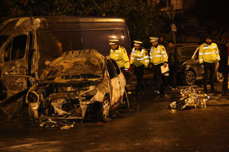 rupture: BUCHAREST, ROMANIA - November 07, 2017: Police, forensics inspect car burned after an accident. Two burnt to death when the car erupted in flames after a drunk driver hit a car and crashed. Editorial