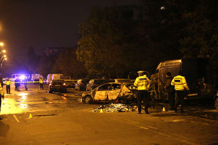 BUCHAREST, ROMANIA - November 07, 2017: Police, forensics inspect car burned after an accident. Two burnt to death when the car erupted in flames after a drunk driver hit a car and crashed. Editorial