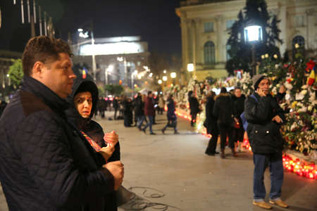 BUCHAREST, ROMANIA  - December 13, 2017: Citizens are bringing flowers and light candles as a last homage to the late Romanian King Michael I, at the former Royal Palace, now National Art Museum. Banque d'images - 91644100