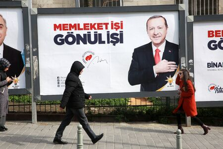 ISTANBUL, TURKEY - March 10, 2018: People walk past by AK Party billboards with pictures of Turkish President Tayyip Erdogan and mayoral candidate Binali Yildirim in Istanbul, Turkey. Редакционное