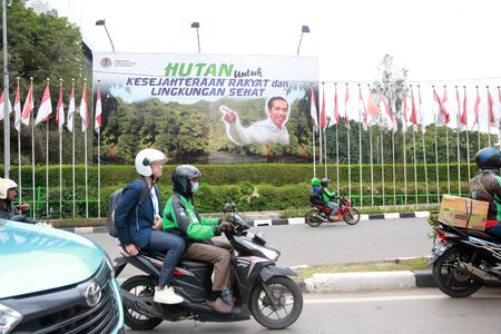 JAKARTA INDONESIA - March 29, 2019: A motorcyclist rides past a large election poster for Indonesian Presidential elections in Jakarta, Indonesia. Редакционное