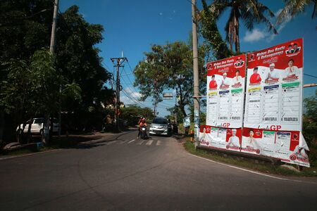 BALI, INDONESIA - April 07, 2019: A motorcyclist rides past a large election poster for Indonesian Presidential elections in Bali, Indonesia. Редакционное