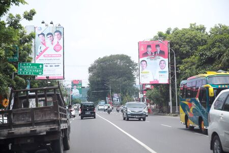 SEMARANG INDONESIA - March 30, 2019: Cars are passing near large election poster for Indonesian Presidential elections in Semarang, Indonesia.