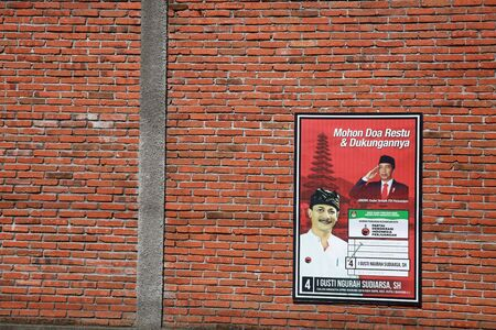 BALI, INDONESIA - April 03, 2019: An election poster for Indonesian Presidential elections is seen on a red brick wall in Bali, Indonesia. Редакционное