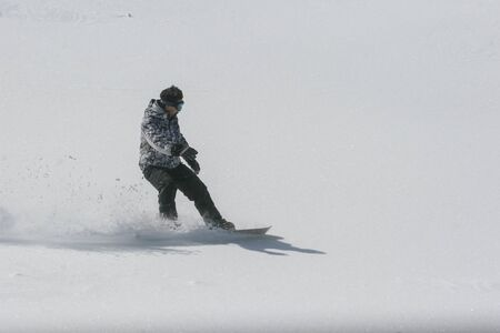 SIBIU, ROMANIA - March 13, 2010: Snowboarder running down the slope in Fagaras mountains.
