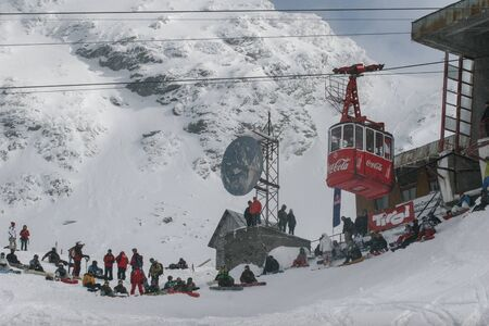 SIBIU, ROMANIA - March 13, 2010: Photo of cable way with Coca-Cola logo in Faragas mountains. Group of people having fun while skiing and snowboarding. Editorial