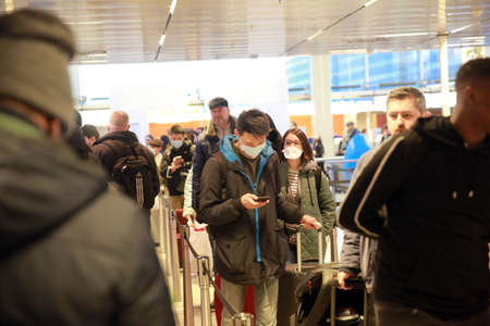 AMSTERDAM, NETHERLANDS - MARCH 13, 2020: People wear protective face mask as a preventive measure against the spread of the coronavirus in Amsterdam Airport Schiphol. 新闻类图片